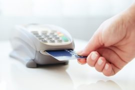 a shopper inserts a payment card into a card reader. Companies that support this service face payment processing marketing challenges.